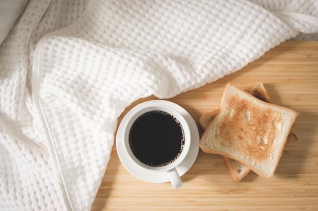 トーストしたパンが付いているベッドに置かれた白いカップのコーヒーパン