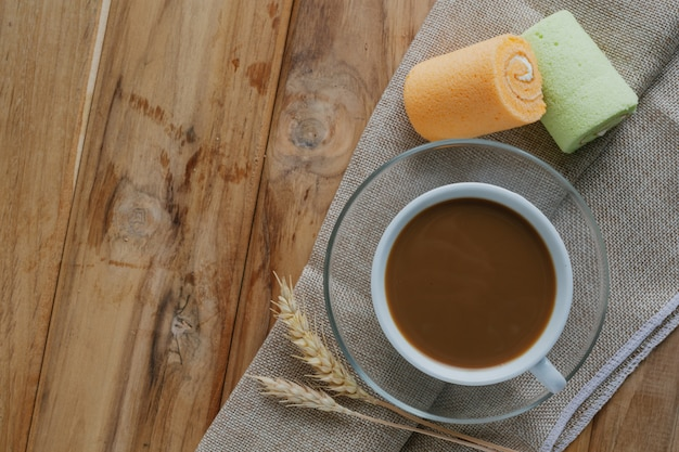 Coffee and bread placed on brown wood floors.