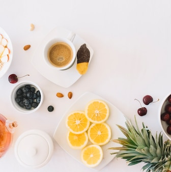 Coffee and bread with fruits on white background