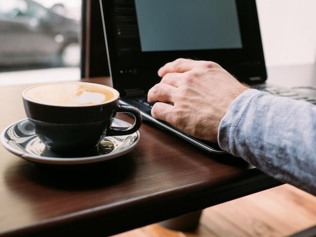 コーヒーブレイクと仕事。ラップトップで入力する男の手