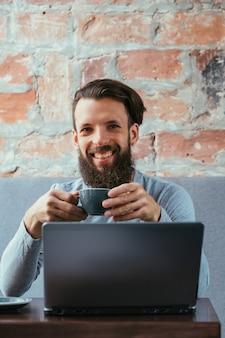 コーヒーブレイクと仕事。ノートパソコンの前に座って温かい飲み物のカップを保持している男。