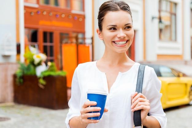 コーヒーブレイク。コーヒーカップを保持し、屋外に立っている間笑顔の魅力的な若い笑顔の女性