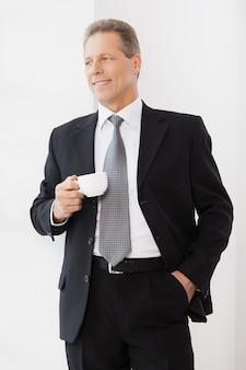 휴식 시간. 커피 컵을 들고 창 근처에 서있는 동안 웃는 formalwear의 쾌활한 수석 남자