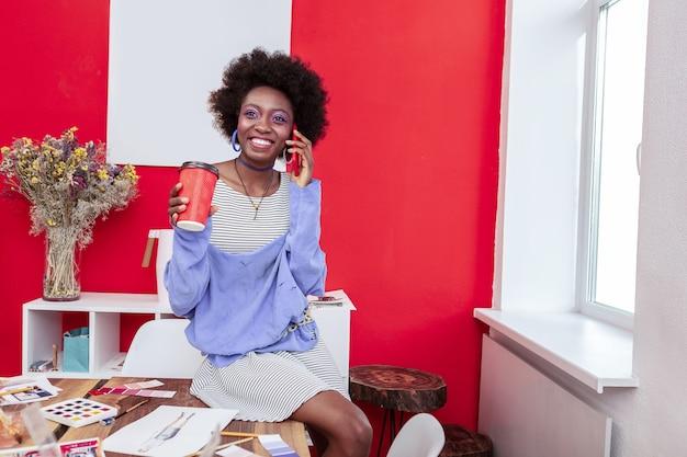 コーヒーブレイク。電話で話している間彼女のコーヒーブレイクを楽しんでいる陽気なスリムなファッションデザイナー
