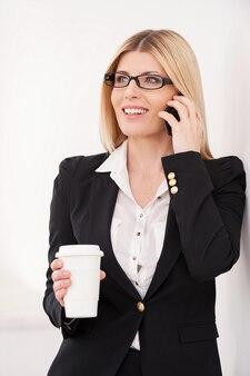 휴식 시간. 자신감이 성숙한 여성 사업가가 휴대전화로 통화하고 커피 컵을 들고 있다