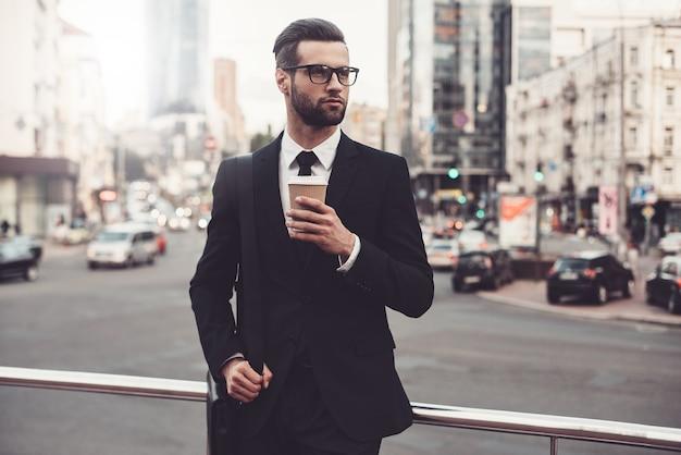 コーヒーブレイク。コーヒーカップを保持し、目をそらしている完全なスーツの自信を持って若い男
