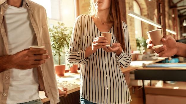 서 있는 동안 커피 컵을 들고 평상복을 입은 젊은 남녀의 커피 브레이크 자른 사진