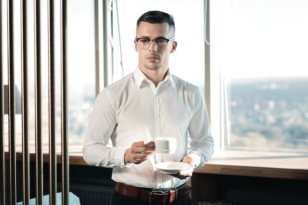 Coffee break. dark-haired handsome businessman having coffee break standing near the window