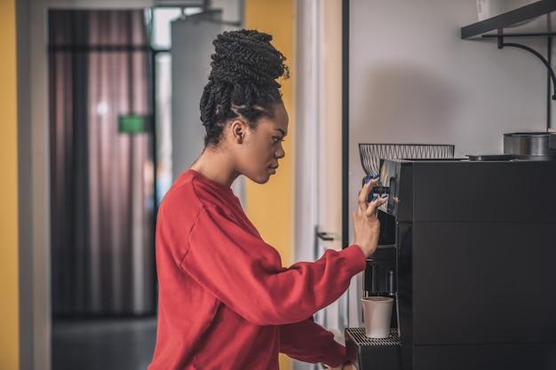 Перерыв на кофе. темнокожая молодая женщина стоит возле кофеварки