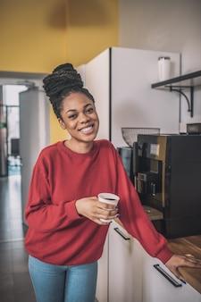 휴식 시간. 커피 기계 근처에 서 어두운 피부 젊은 여자