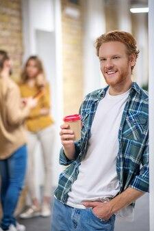 휴식 시간. 복도에 서서 커피 한 잔을 들고 생강 남자