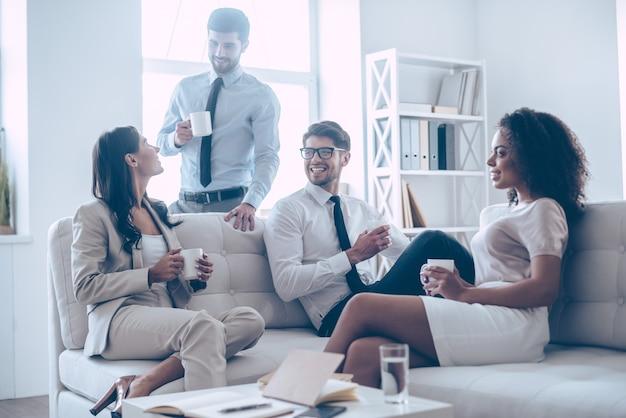 Перерыв на кофе. группа из четырех молодых людей держит чашки кофе и обсуждает что-то с улыбкой, сидя на диване в офисе