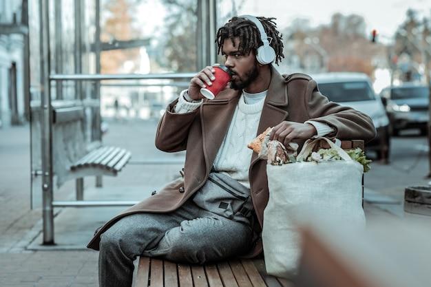 コーヒーブレイク。音楽を聴きながらベンチに座っているハンサムなひげを生やした男性