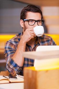 コーヒーブレイク。コーヒーを飲みながら、コーヒーショップに座ってカメラを見ているハンサムな若い男