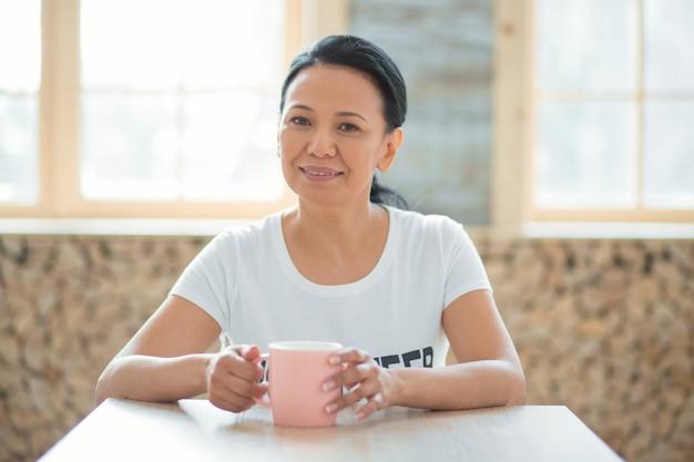 휴식 시간. 행복 기쁜 여성 자원 봉사자 테이블에 앉아 카메라를 보면서 커피를 즐기는