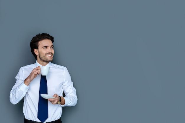 휴식 시간. 직장에서 휴식을 취하는 동안 웃고 그의 커피를 즐기는 즐거운 긍정적 인 잘 생긴 남자