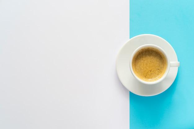 휴식 시간. 한 잔의 커피와 최소한의 흰색과 파란색 배경 템플릿. 공간을 복사하십시오. 프리미엄 사진