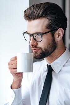 휴식 시간. 커피를 마시고 사무실에 서있는 동안 멀리 바라보는 안경에 잠겨있는 젊은 사업가
