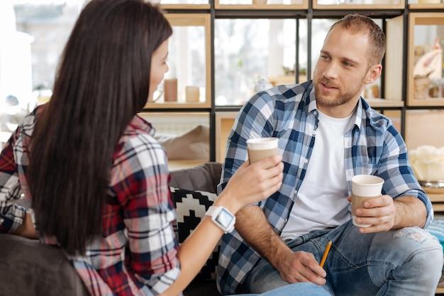 コーヒーブレイク。一緒に座って、お互いに話している間コーヒーを飲んでいる楽しい素敵な格好良い同僚