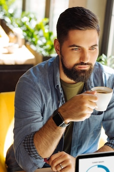 Coffee break. serious bearded man sitting with a coffee cup while having a coffee break