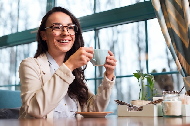 Coffee break. smart pleasant cheerful woman sitting at the table while smiling and holding coffee