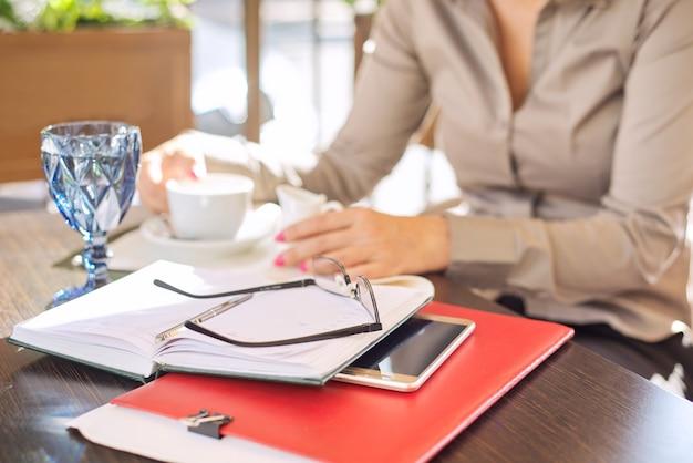 Перерыв на кофе. столик в ресторане на открытом воздухе, деловые бумаги, блокнот, смартфон, очки, чашка кофе. деловая женщина в расфокусе