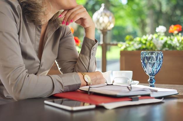 Кофе-брейк, столик в ресторане на открытом воздухе, деловые бумаги, ноутбук, смартфон, очки, чашка кофе. отдыхающая деловая женщина