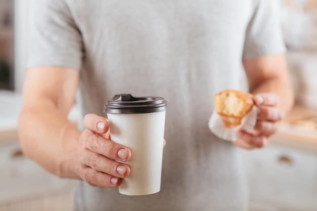 휴식 시간. 가져가. 뜨거운 음료와 머핀과 일회용 모형 컵을 들고 남자.