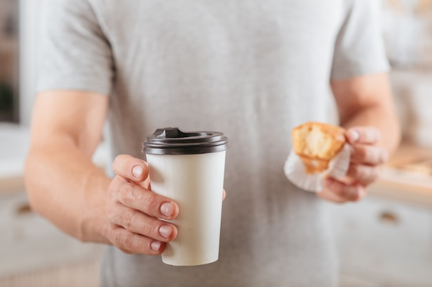 Coffee break. take away. man holding muffin and disposable mockup cup with hot drink.