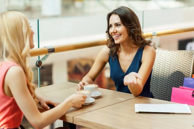 Перерыв на кофе. две красивые молодые женщины отдыхают во время похода по магазинам
