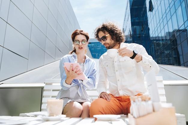 コーヒーブレイク。コーヒーブレイクを一緒に過ごしている間、休息を感じている2人の創造的なプロのマネージャー