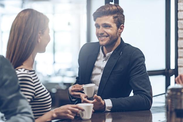 Перерыв на кофе с коллегой. молодой красивый мужчина держит чашку кофе и обсуждает что-то с молодой женщиной, стоя у барной стойки