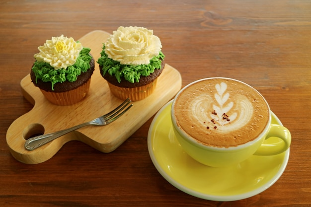 Coffee break with a cup of hot cappuccino and two cupcakes topped with flower shaped whipped cream
