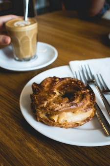 Coffee break with delicious pastry in a coffeeshop