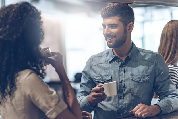 Кофе-брейк от радости. молодой красивый мужчина держит чашку кофе и обсуждает что-то с молодой женщиной, стоя у барной стойки