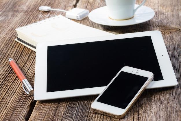 나무 테이블에 전화 및 태블릿 커피 브레이크