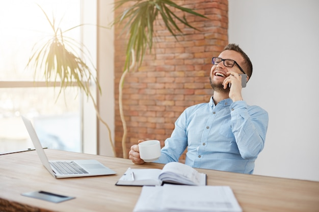 Coffee break on work. adult shaved businessman in glasses sitting in comfortable office