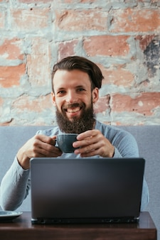 Coffee break and work. man holding a cup of hot drink sitting in front of laptop.