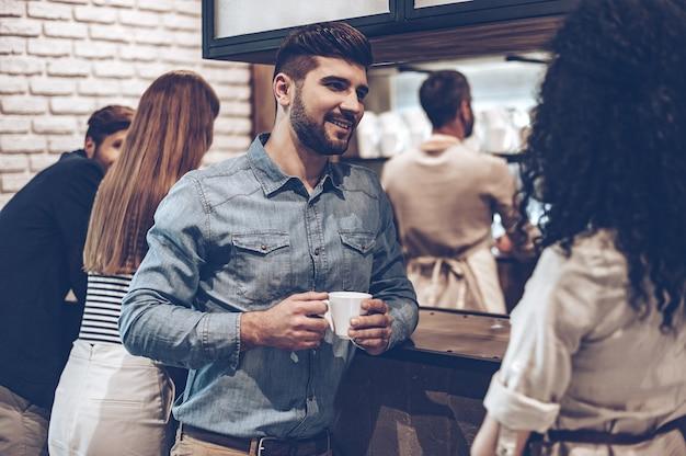 Перерыв на кофе. молодой красивый мужчина держит чашку кофе и обсуждает что-то с молодой женщиной, стоя у барной стойки