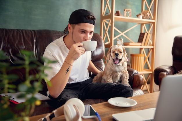 Перерыв на кофе. молодой человек сидит на коричневом диване со своей милой собакой, домашним американским кокер-спаниелем во время карантина по коронавирусу или covid-19. уютное офисное рабочее место, удаленная работа, концепция электронного обучения.