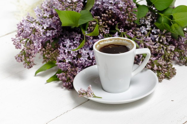 Coffee for breakfast and lilac flowers. selective focus