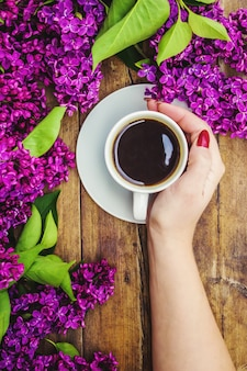Coffee for breakfast and lilac flowers. selective focus.