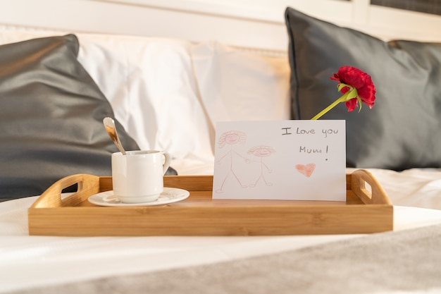 Coffee and breakfast prepared on a tray with a letter and flower as a gift for mother's day