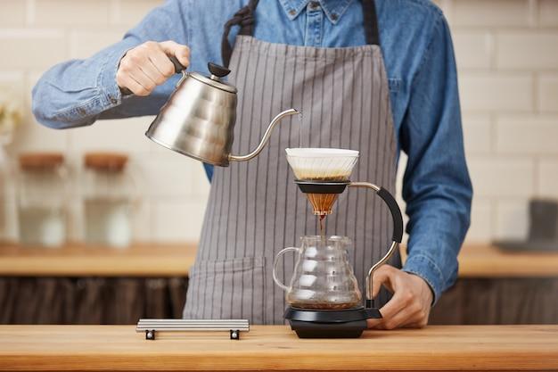 Кофейные гаджеты. мужской бармен, заваривающий кофе плун в баре.
