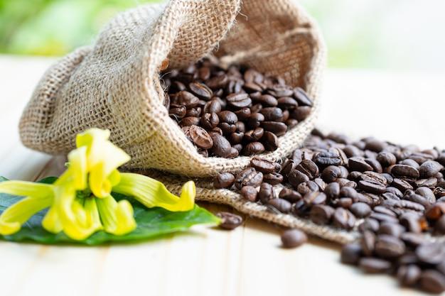 新鮮な緑の葉の袋にローストしたコーヒーブラウン豆ミディアム