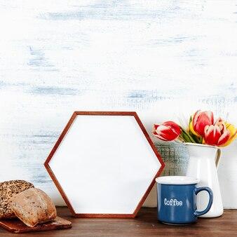 Caffè e panini vicino a fiori e cornice