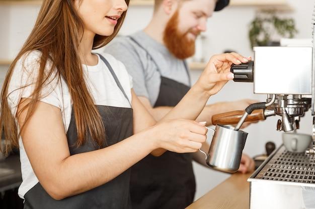 Бизнес-концепция кофе - портрет леди-бариста в фартуке, готовящей и дымящегося молоко для заказа кофе со своим партнером, стоя в кафе.