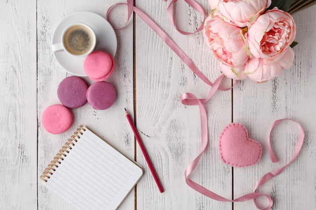 Coffee, cake macaron, clean notebook, eyeglasses and flower on pink table from above.
