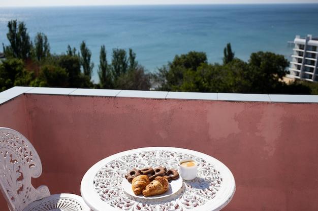 Кофе, пирожные и печенье на тарелке на красивой террасе со стульями и столом с прекрасным видом на море.