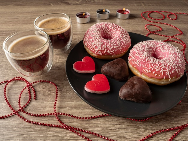 Coffee and candles behind a plate with donuts and heart-shaped cookies and a ribbon on the table in front of the plate